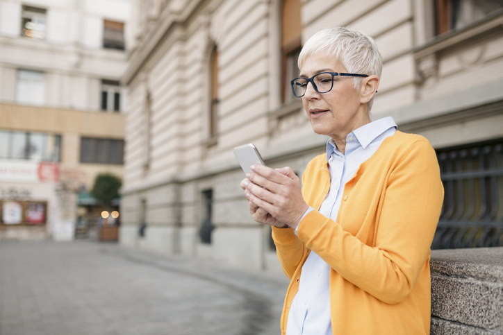 Senior Caucasian woman with gray hair, holding a smart phone and looking worried, reserved and restrained